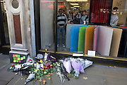 Youths from inside London's Apple store look at the  makeshift shrine, where Londoners commemorate Apple's creator Steve Jobs the morning after hearing of his death overnight from pancreatic cancer  at the age of 56 on the 6th Oct 2011. This Apple Store in the capital's Regent's Street was the first to be built in Europe and serves as a flagship outlet for the stylish brand of computer accessories that were largely the brainchild of Jobs who started the company as a student in 1977.