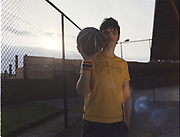 Young man holding a basketball near his face.
