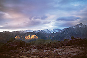 Weather: Sunset light breaks through the clouds illuminating the mountains near Lone Pine along Route 395 in the Eastern Sierras of California.  (1990)