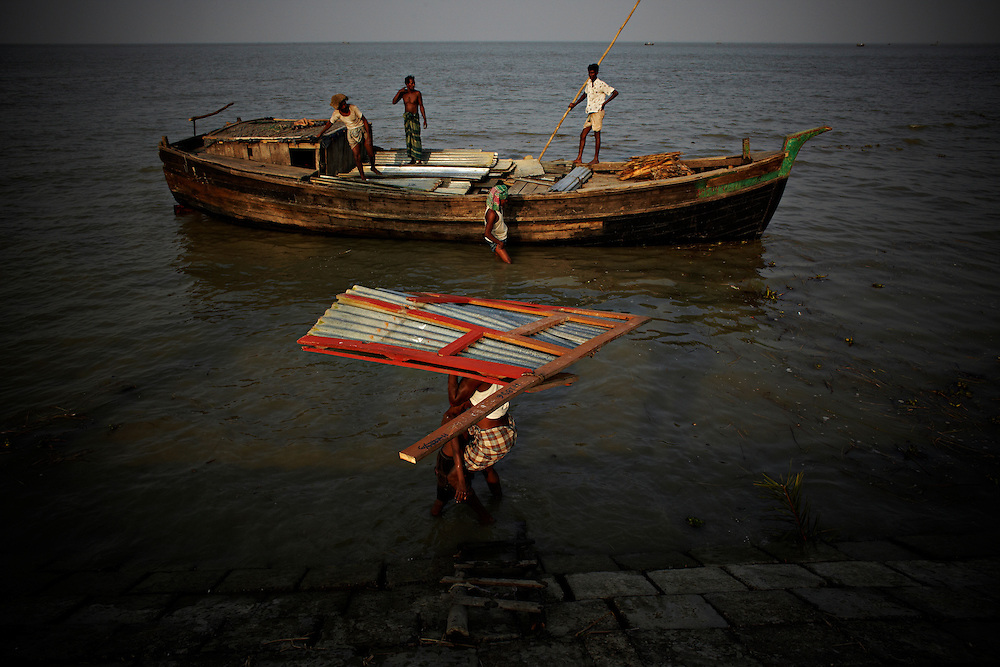 """The house of Khorshed Awladad is being moved as the river has been closing in. """"I'm moving because I'm loosing my house"""" he said.. ?This area in the south of Bangladesh has been called ground zero of climate-change due to heavy river and ocean erosion. The lowlying area is also hugely affected by cyclones and rising sea-levels...By the Mouth of Ganges, at the Bay of Bengal is the Island of Bhola. This home of about two million people is considered to be ground zero of climate change. Half the island has disappeared in the past 40 years, and according to scientists the pace is not going to slow down. People pack up and leave as the water get closer. Some to a nearby embankment, while those with enough money move further inland, but for most life move on until the inevitable. It's always about survival for the people in one of the worlds poorest countries...Photo by: Eivind H. Natvig/MOMENT"""