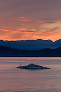 One of the Grebe Islets in British Columbia's Howe Sound.  Photographed at sunset from Juniper Point at Lighthouse Park in West Vancouver, British Columbia, Canada. In the background you can see Bowen Island, and the mountain peaks in the Sunshine Coast's Tetrahedron Range.