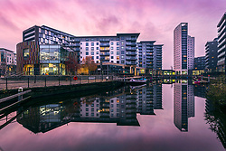 © Licensed to London News Pictures. 20/11/2019. Leeds UK. The sky turns pastel pink at dawn this morning in Leeds Dock in Leeds city centre. The dock was built in 1843 & used to bring coal from collieries around Rothwell & Wakefield to supply heavy industries in Leeds City Centre, the dock is now a retail, office & residential area. Photo credit: Andrew McCaren/LNP