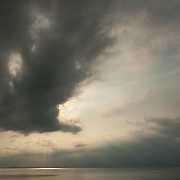Ominous clouds obscure the setting sun over Ipswich Bay in Massachusetts
