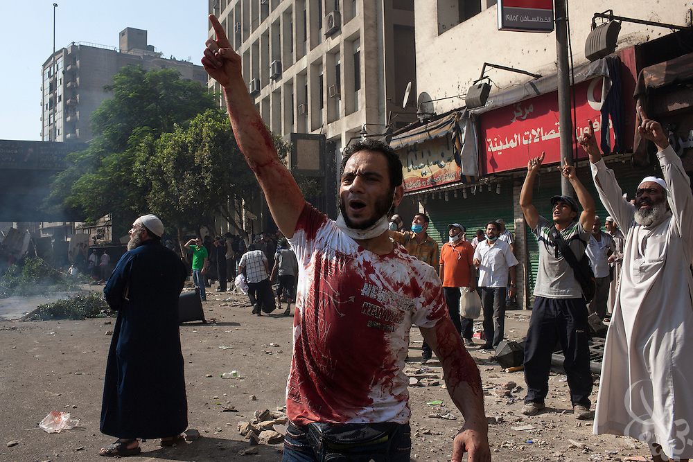 """Supporters of deposed Egyptian President Mohamed Morsi shout praises to God as a military helicopter flies overhead during intense street clashes during the August 16, 2014 """"Day of Rage"""" protests in Cairo, Egypt."""