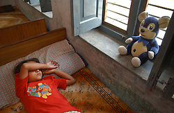 NEPALGANJ, NEPAL, APRIL 14, 2004: A Nepali girl,  who was orphaned because of the Maoist insurgency sleeps inside the Sahara orphanage in Nepalganj, Nepal April 14, 2004.   (Ami Vitale/Getty Images)