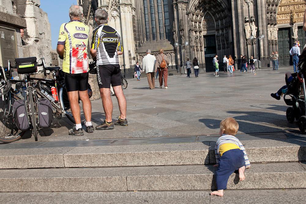 Europe, Germany, Cologne, boy on steps at the Cathedral square, bicycle driver...Europe, Deutschland, Koeln, Junge krabbelt Stufen zur Domplatte rauf, Fahrradfahrer.