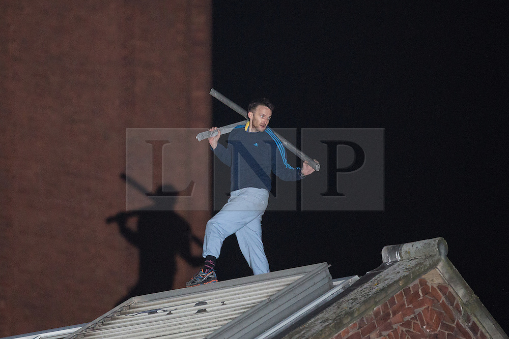 © Licensed to London News Pictures . 14/09/2015. Manchester, UK. An inmate at HMP Manchester ( Strangeways Prison ) , named as STUART HORNER , on the roof with a piece of metal after climbing a fence and up on to the roof , in protest of conditions inside . Photo credit : Joel Goodman/LNP