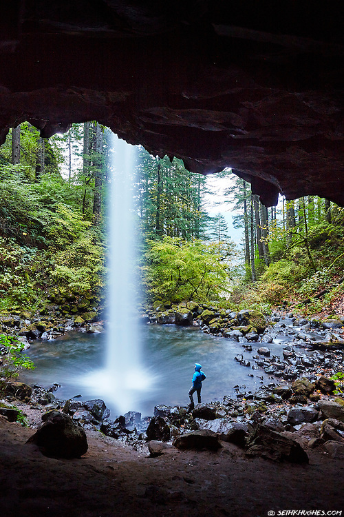 A hiker stands beneath Upper Horsetail Falls and admires the grandeur of the waterfall from the pool below.