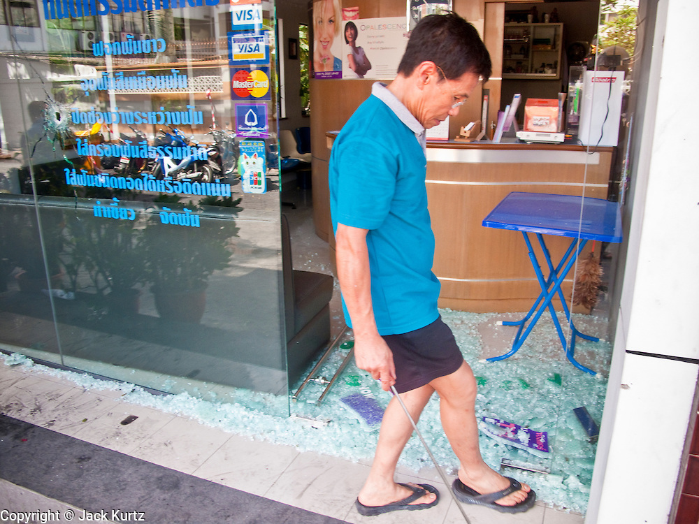 21 MAY 2010 - BANGKOK, THAILAND: A dentist closed his practice after unidentified snipers shot up the front of his practice during anti government violence Wednesday. Clean up continued in Bangkok Friday, two days after the army cleared the streets of anti government protesters.  PHOTO BY JACK KURTZ