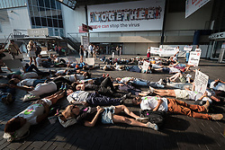 26 July 2018, Amsterdam, the Netherlands: At a die-in demonstration by the entrance of the 2018 International AIDS Conference, a people hold signs criticizing the war on drug users being conducted by Philippines President Rodrigo Duterte.