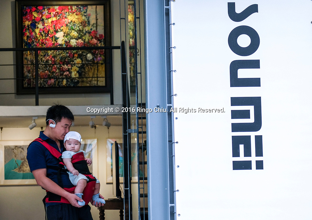 A man carries a baby visits a gallery at the M50 Art Colony in Shanghai, China. Shanghai is the most populous city in China and the most populous city proper in the world. It is one of the four direct-controlled municipalities of China, with a population of more than 24 million as of 2014. It is a global financial centre, and a transport hub with the world's busiest container port. Located in the Yangtze River Delta in East China, Shanghai sits on the south edge of the mouth of the Yangtze in the middle portion of the Chinese coast. The municipality borders the provinces of Jiangsu and Zhejiang to the north, south and west, and is bounded to the east by the East China Sea. A major administrative, shipping, and trading town, Shanghai grew in importance in the 19th century due to trade and recognition of its favourable port location and economic potential. The city was one of five forced open to foreign trade following the British victory over China in the First Opium War while the subsequent 1842 Treaty of Nanking and 1844 Treaty of Whampoa allowed the establishment of the Shanghai International Settlement and the French Concession. The city then flourished as a center of commerce between China and other parts of the world (predominantly Western countries), and became the primary financial hub of the Asia-Pacific region in the 1930s. However, with the Communist Party takeover of the mainland in 1949, trade was limited to socialist countries, and the city's global influence declined. In the 1990s, the economic reforms introduced by Deng Xiaoping resulted in an intense re-development of the city, aiding the return of finance and foreign investment to the city. Shanghai has been described as the &quot;showpiece&quot; of the booming economy of mainland China; renowned for its Lujiazui skyline, museums and historic buildings, such as those along The Bund, the City God Temple and the Yu Garden.(Photo by Ringo Chiu/PHOTOFORMULA.com)<br /> <br /> Usage Notes: This content is intended for editoria
