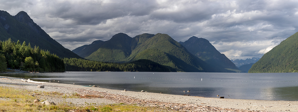 View of the beach and swimming area at Alouette Lake at Golden Ears Provincial Park in Maple Ridge, British Columbia, Canada. Peaks in the background include Evans Peak (left), Mount Nutt, Mount Gatey, Mount Clarke and Mount Ratney (back, right).