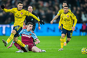 Ainsley Maitland-Niles (Arsenal) & Declan Rice (West Ham) look on as the ball leaves them during the Premier League match between West Ham United and Arsenal at the London Stadium, London, England on 9 December 2019.