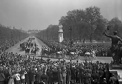 The cheering crowds line the route as King George VI and Queen Elizabeth, and Princess Margaret, return down the Mall to Buckingham Palace from St Paul's Cathedral. A part of the Victoria Memorial can be seen to the right.