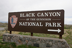 Welcome sign outside of Black Canyon of the Gunnison National Park is a United States National Park located near Montrose, Colorado in the western part of the state. The park is managed by the National Park Service. There are two entrances to the park; the more-developed south rim entrance is located 15 miles (24 km) east of Montrose, while the north rim entrance is located 11 miles (18 km) south of Crawford and is closed in the winter. The park contains 12 miles of the 48 mile long canyon of the Gunnison river. The park contains the deepest and most dramatic section of the canyon, one of the deepest mountain descents in North America.  The canyon continues upstream into the Curecanti National Recreation Area and downstream into the Gunnison Gorge National Conservation Area.