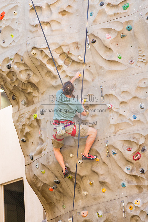 A man climbs a rock climbing wall in downtown Asheville, North Carolina.