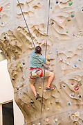 A man climbs a rock climbing wall in downtown Asheville, North Carolina.