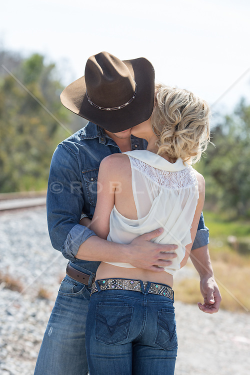 beautiful woman and a sexy cowboy together outdoors being affectionate