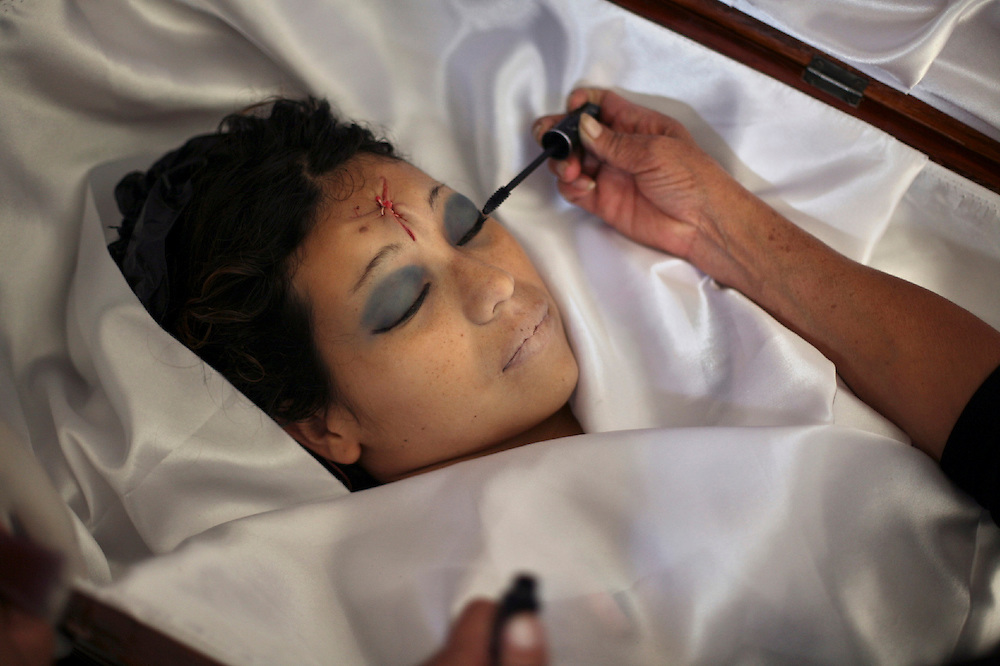 Marta Reyes applies makeup to the corpse Dina, her murdered daughter, in the &quot;Lopez&quot; funeral home, Guatemala City, Thursday, May 19, 2009. <br /> Guatemala's constant streak of murders ,17-a-day,  provide a steady flow of customers to unregulated  funeral homes, where funeral workers can embalm corpses in the back of auto repair shop or rush to crime scenes to gather information that will allow them to locate, notify and make a sales pitch to the bereaved relatives.