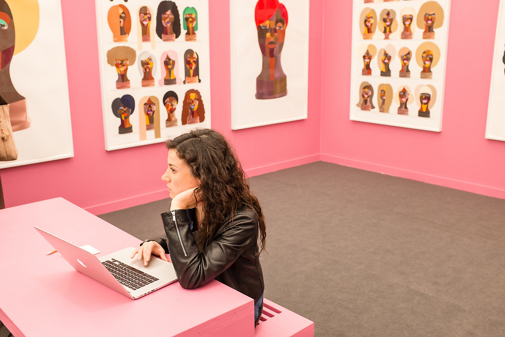 New York, NY - May 3, 2019. Derrick Adams's work on pink walls in London's Vigo Gallery booth Spectators at the Frieze Art Fair on New York City's Randalls Island.