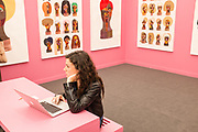 New York, NY - May 3, 2019. Derrick Adams's work on pink walls in London's Vigo Gallery booth Spectators at the Frieze Art Fair on New York City's Randalls Island.