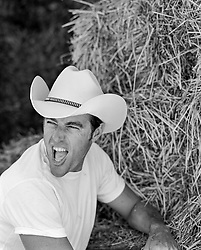 cowboy yelling while leaning against bales of hay