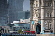 A London bus crosses the Thames river through the south main tower of the Victorian-era Tower Bridge, and in the background is the modern Walkie Talkie building (aka 20 Fenchurch Street), on 14th September 2017, in London, England.