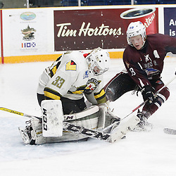 "TRENTON, ON  - MAY 3,  2017: Canadian Junior Hockey League, Central Canadian Jr. ""A"" Championship. The Dudley Hewitt Cup. Game 3 between Powassan Voodoos and the Dryden GM Ice Dogs.  Nate McDonald #33 of the Powassan Voodoos makes the save as  Woody Galbraith #18 of the Dryden GM Ice Dogs  drives to the net during the second period.<br /> (Photo by Tim Bates / OJHL Images)"