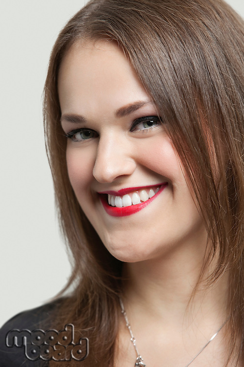 Close-up portrait of a beautiful woman with red lips smiling over gray background