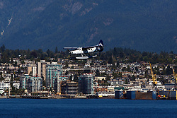 De Havilland Canada DHC-3T Otter (C-GHAZ) operated by Harbour Air with the Vancouver Whitecaps Livery lands in Vancouver Harbor, Vancouver, British Columbia, Canada