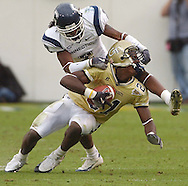 ATLANTA,GA: GA: Connecticut's JUSTIN PERKINS (2) pulls CALVIN JOHNSON'S (21) face mask after he caught the ball for a first down in the 4th quarter on Saturday,11/13/04 at Georgia Tech.  TECH won the game 30 to 10.  ©2004 Johnny Crawford