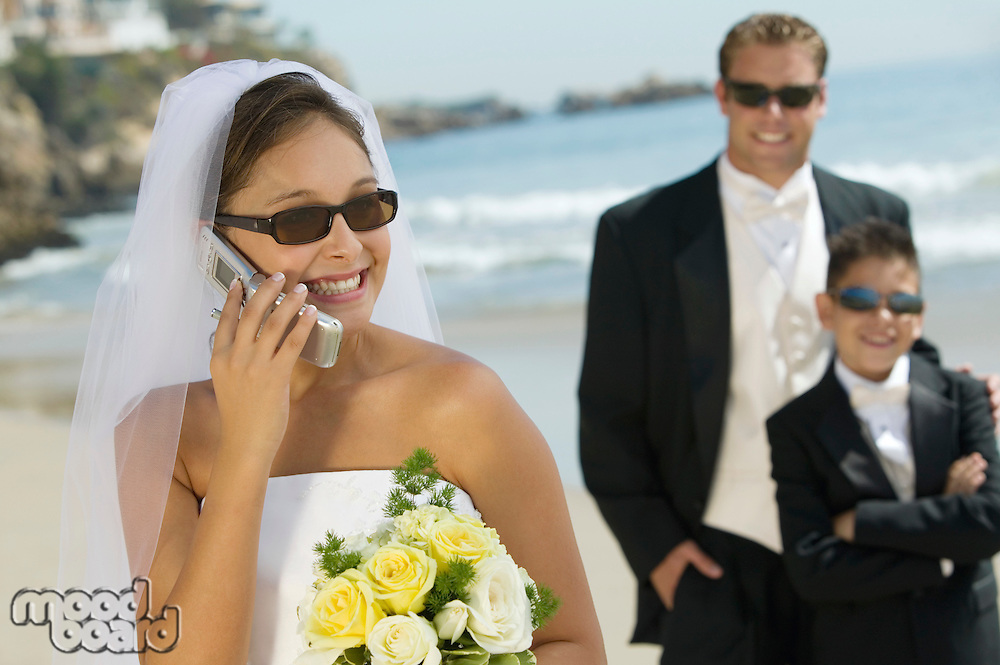 Bride using mobile phone Groom and brother in background