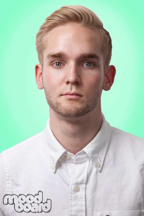 Portrait of young Caucasian man against green background