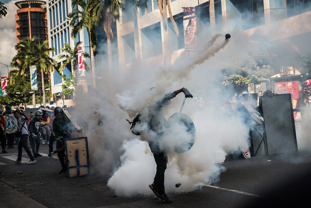 CARACAS, VENEZUELA - MAY 20, 2017: An anti-government protester throws a tear gas canister back at members of the National Police, who had previously shot it at a group of protesters during clashes in Caracas. The streets of Caracas and other cities across Venezuela have been filled with tens of thousands of demonstrators for nearly 100 days of massive protests, held since April 1st. Protesters are enraged at the government for becoming an increasingly repressive, authoritarian regime that has delayed elections, used armed government loyalist to threaten dissidents, called for the Constitution to be re-written to favor them, jailed and tortured protesters and members of the political opposition, and whose corruption and failed economic policy has caused the current economic crisis that has led to widespread food and medicine shortages across the country.  Independent local media report nearly 100 people have been killed during protests and protest-related riots and looting.  The government currently only officially reports 75 deaths.  Over 2,000 people have been injured, and over 3,000 protesters have been detained by authorities.  PHOTO: Meridith Kohut