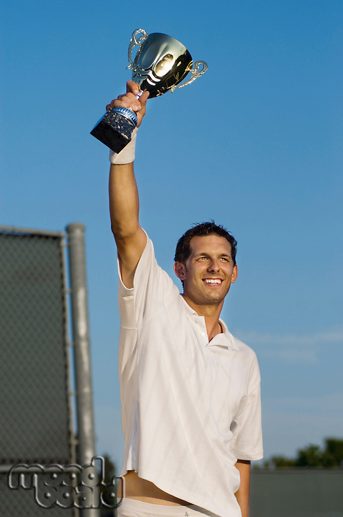 Tennis Player Proudly Holding Trophy in Air