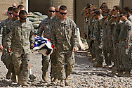 FOB COBRA, IRAQ - JUNE 11: US soldiers carry the body of a US soldier killed in a car bomb attack during a memorial ceremony, on June 11, 2010, on FOB Cobra, near Jalula, Diyala Province, Iraq. Specialists William C. Yauch (23) of Batesville, Arkansas and Israel P. Obryan (24) of Newbern, Tennessee, from Charlie Company, 5th BN, 20th Infantry Reg, 3rd Stryker Brigade Combat Team, 2nd Infantry Division were killed along with 2 civilians and 1 Iraqi policeman when a car bomb drove into their patrol. Iraq faces multiple challenges in the lead-up to the drawn-down of US forces in Iraq, with many observers claiming that while they have the capablities of handling home-grown problems, they are far from being able to tackle external threats. Political wrangling has reportedly fostered greater instability throughout the country with fears of renewed sectarian violence breaking out as insurgents set-up attacks in an attempt to exploit vulnerabilities amongst the populace. (Photo by Warrick Page)