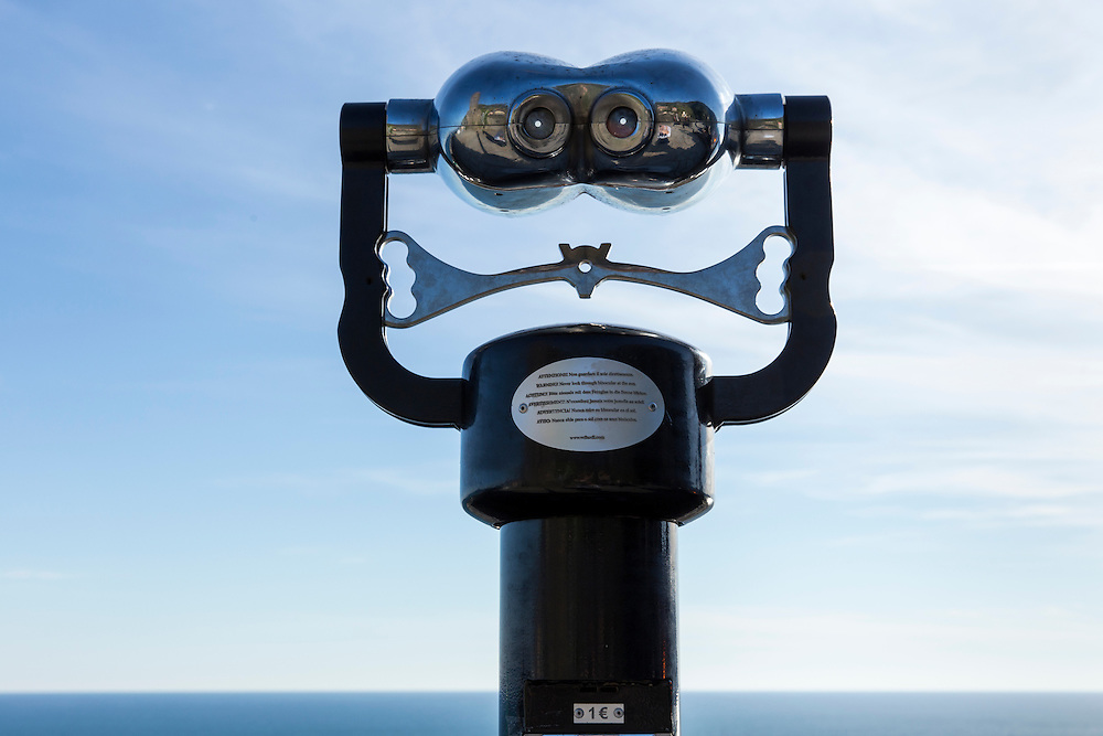 Italy, La Spezie, Viewing binoculars on stand overlooking Mediterranean Sea in waterfront village of Vernazza in Cinque Terre on spring afternoon.