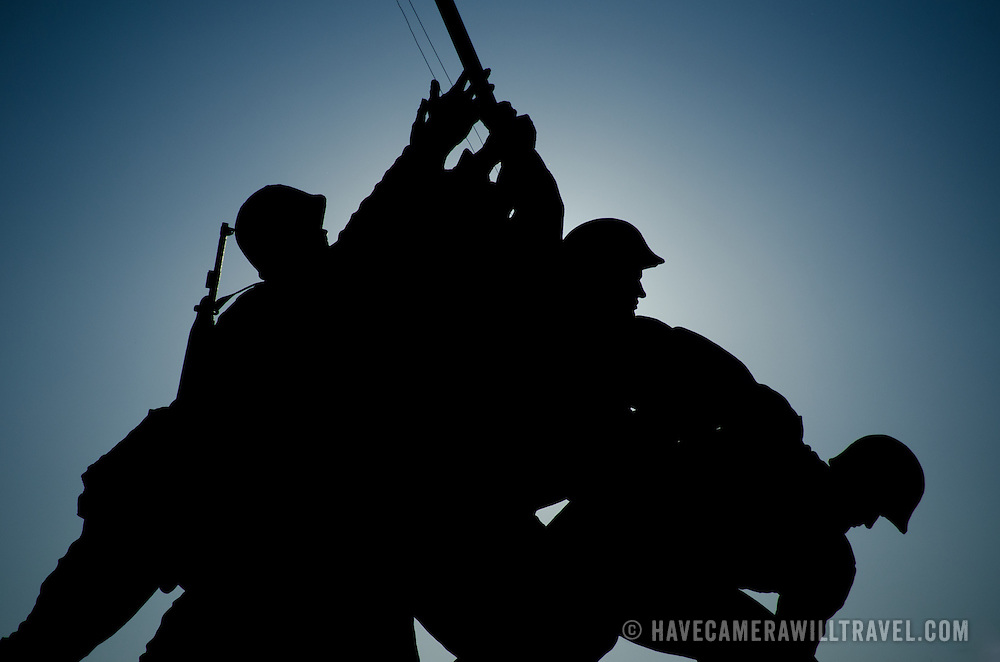 The sun rises behind a silhouette of the Iwo Jima Memorial (US Marine Corps Memorial) in Arlington, Virginia. The large bronze statue is based on a photograph by AP photographer Joe Rosenthal of the US claiming the island of Iwo Jima in the Pacific Theater of World War II.