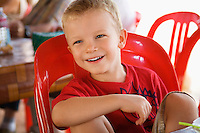 Little Boy Sitting in Red Plastic Chair