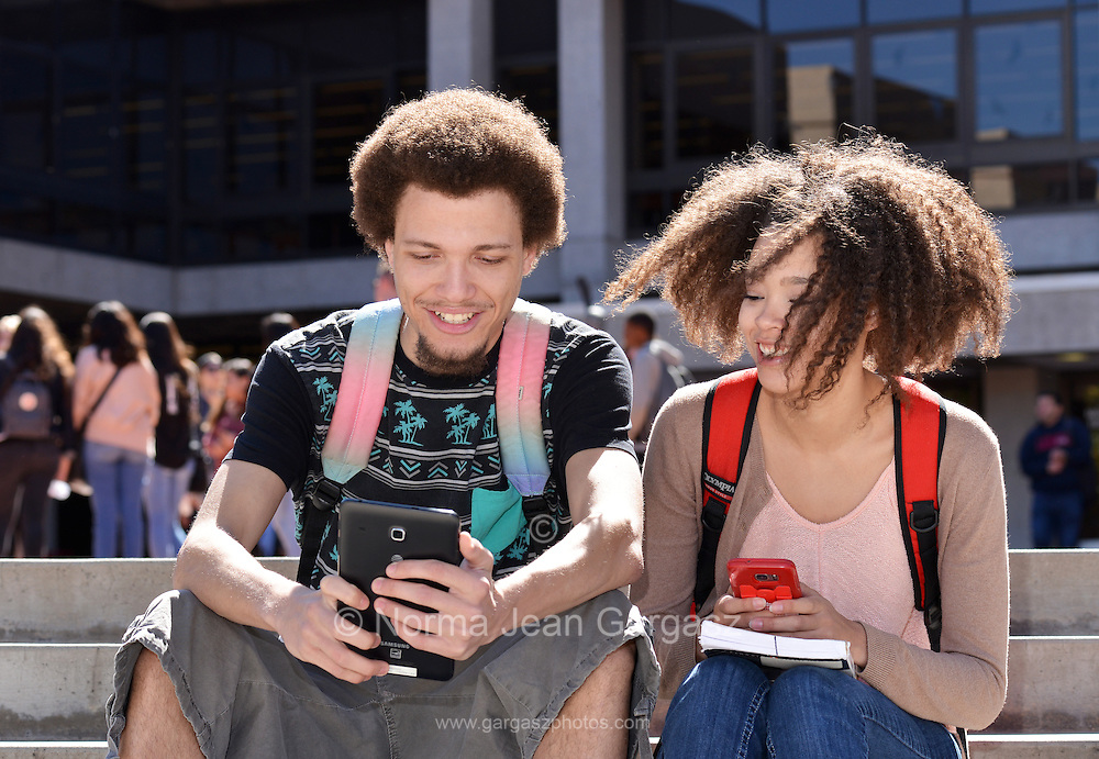 A young woman and man with books and electronics on a college campus.