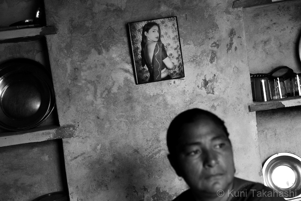 A sex worker sits under the old photograph of herselft at house in Ingonia in Rajasthan, India on Nov 16, 2009. ..
