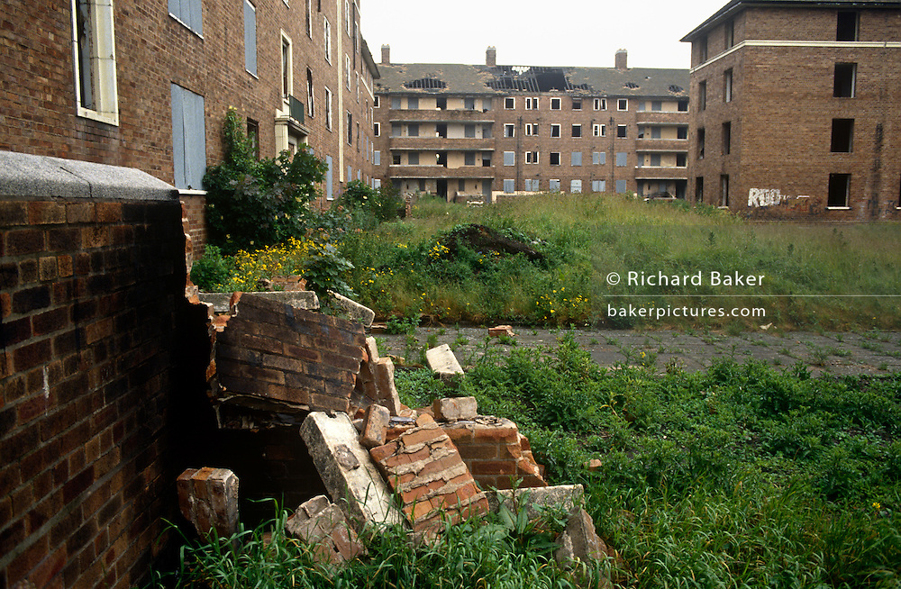 A low, wide landscape of dereliction and poverty on a Toxteth estate during the early 1990s in the city of Liverpool, England. With a crumbling brick wall now fallen on to long grass in the foreground and in the distance, the remains of former homes with gaping holes in roofs, now derelict and awaiting demolition now that all residents have left, their community dispersed to other nearby estates, an impoverished population having moved out for a better life elsewhere.