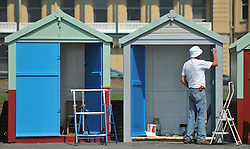 © licensed to London News Pictures. BRIGHTON  UK. 21/04/11.A  man paints a beach hut. People flock to Brighton Beach today (21 April 11) to catch the sunshine before the start of the Easter Bank Holiday in Britain. Temperatures are set to continue to rise over the weekend. Photo credit should read Stephen Simpson/LNP