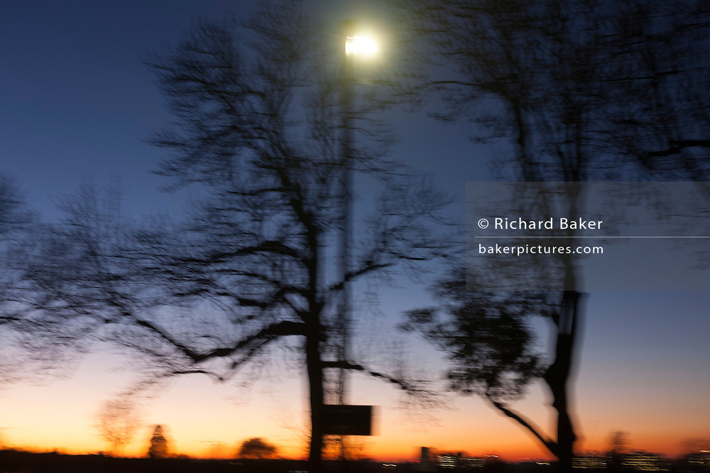 A blurred landscape of park trees and the glow immediately after a sunset, on 29th November 2016, in Herne Hill, south London borough of Lambeth, London, England.