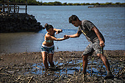 Karina Jacany gets a helping hand from Kai Kahoaliki Fonseca after getting stuck in the fishpond mud.
