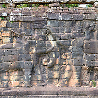 Elephant Bas-reliefs at Angkor Thom in Angkor Archaeological Park, Cambodia<br /> Along the eastern enclosure of the Royal Palace grounds containing the Phimeanakas is the Elephant Terrace. This was the reviewing platform for King Jayavarman VII to watch parades, public events and welcome back his victorious soldiers. The nearly ten foot high wall is decorated with bas-reliefs such as these elephants portrayed in battle. Other elephant carvings show them being led by their mahouts (trainers). More carving themes include garudas, warriors with lion heads plus scenes from sporting events.