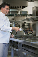 Chef cooking food using frying pan in kitchen