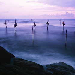 Fishermen perched on permanent stilts fish in the turbulent shallows on the Weligama coast of Sri Lanka.