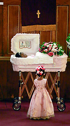 07 September 2013. New Hope Baptist Church. New Orleans, Louisiana. <br /> Paris Samuels looks up to the coffin of her sister, 1 year old toddler Londyn Unique Reed Samuels. The infant Londyn was shot to death August 29th by thugs whilst in the arms of her babysitter, the intended victim who was holding Londyn whilst walking down the street at the time of the assault. NOPD has arrested 2 men in connection with the heinous crime.<br /> Photo; Charlie Varley