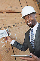 Portrait of happy African American male contractor using tablet PC while inspecting wooden planks